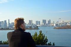 Young man looking at the Rainbow Bridge in Tokyo City.Japan. Royalty Free Stock Photos