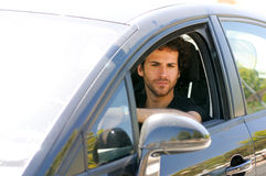 Young man looking in the rearview mirror Stock Photos