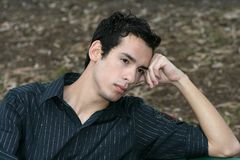 Young man looking sad. A young man sitting on a bench and looking sad Royalty Free Stock Image