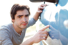 Young man looking for scratches on his car Stock Photo
