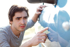 Young man looking for scratches on his car Royalty Free Stock Images