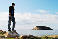 Young man looking at the sea. A young man standing on a rock with eyes on the horizon Royalty Free Stock Image