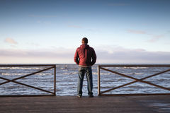 Young man looking on the sea from wooden pier Royalty Free Stock Image