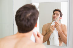 Young man looking at self in bathroom mirror Stock Photo