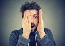 Young man looking shocked, surprised in disbelief, with hands on face. Portrait of a young man looking shocked, surprised in disbelief, with hands on face Stock Image