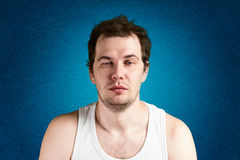 Young man looking sleepy. On the blue background Royalty Free Stock Images
