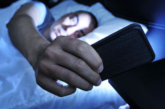 Young man looking at the smartphone in bed at night royalty free stock images