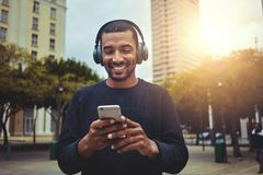 Young man looking at smartphone with headphone on his head stock photography