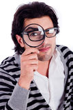 Young man looking straight with a magnifying glass. In isolated white background royalty free stock photography