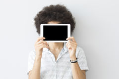 Young man looking at a tablet on his face. Young man looking  at a tablet on his face Royalty Free Stock Photography