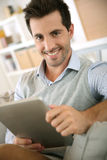 Young man looking at tablet from sofa Stock Images