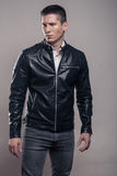 Young man, looking tense, badass, leather jacket,. One young adult man only, badass, looking tense sideways, leather jacket, studio, gray background stock images
