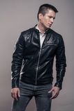 Young man, looking tense sideways, leather jacket,. One young adult man only, badass, looking tense sideways, leather jacket, studio, gray background royalty free stock photography