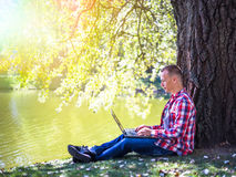 Young man looking to his laptop in city park outdoor. Man in red short smiling Stock Images