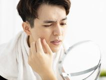 Young man looking to mirror and squeezing pimple royalty free stock photo