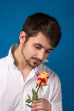 Young man looking to red rose Royalty Free Stock Photography