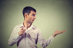 Young man looking to side while pointing at you camera, surprised Stock Images