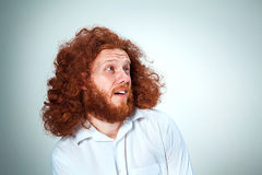 The young man looking to the side. The young smiling man with long red hair looking to the side Stock Images