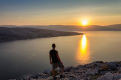 Young man looking to sunrise at sea, Croatia royalty free stock image