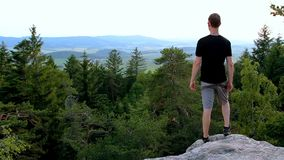 Young man looking to valley from rock, relax in landscape.  stock video