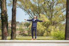 Young man, looking up above, arms outstreched. Young man, looking up above, standing on wall, arms outstreched, sunny day outdoors nature, formal clothes suit Stock Photos