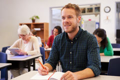 Young man looking up at the board at adult education class Stock Photos