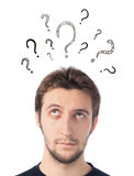 Young man looking up with question marks Royalty Free Stock Images