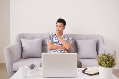 Young man looking up while working on laptop at home Stock Photography