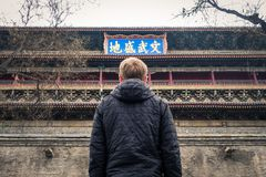 Young Man Looking Up at Xi'an Belltower Chinese Symbols Feeling Royalty Free Stock Photo