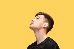 The young man looking up. On yellow studio background Royalty Free Stock Image
