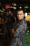 Young man looking at viewer. Portrait of smiling young Hispanic man next to billiards table at pub Stock Photos
