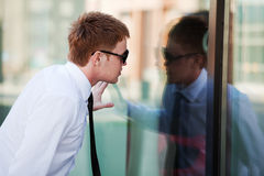 Young man looking through a window Royalty Free Stock Photos