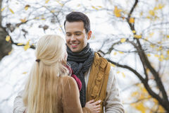 Young man looking at woman in park during autumn Stock Images