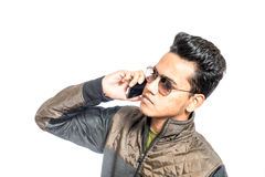 Young man looking worried while using a cellphone. Portrait of a unhappy, young man on the mobile phone against white background Stock Photos