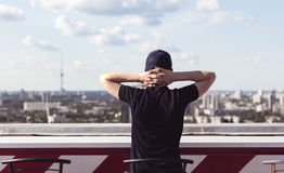 Young man on the roof of a tall building Royalty Free Stock Images