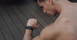 A young man looks at the clock and do exercises. stock footage