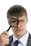 Young man looks through a magnifying glass Royalty Free Stock Photos