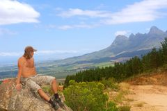 Young man looks at mountains. Young man looks at amazing mountains. Shot in Hottentots Holland Mountains, Vergelegen area, near Somerset West, Western Cape Stock Photos