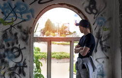 Young man looks into an old broken window. On the street Stock Photography