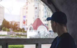 Young man looks into an old broken window. On the street Stock Photos