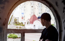 Young man looks into an old broken window. On the street Royalty Free Stock Photos