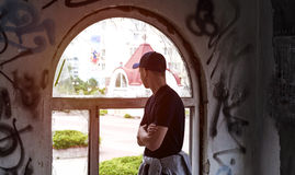 Young man looks into an old broken window. On the street Royalty Free Stock Images