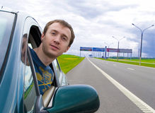The young man looks out of car window. The young man looks out of a car window on road Royalty Free Stock Photography