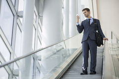 Executive Looks Through Phone on Modern Office Building Escalator Royalty Free Stock Photos