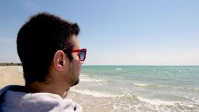 Young man looks at the sea and talks on cellphone on sandy turquoise water beach, Halkidiki Greece. Young man looks at the sea and talks on cellphone on sandy stock video footage