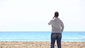 Young man looks at the sea and talks on cellphone on sandy turquoise water beach, Halkidiki Greece. Young man looks at the sea and talks on cellphone on sandy stock footage