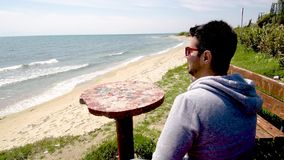Young man looks at the sea, sitting and talking on cellphone on sandy beach, Halkidiki Greece. Young man looks at the sea and talks on cellphone on sandy stock footage