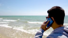 Young man looks at the sea and talks on cellphone on sandy turquoise water beach, Halkidiki Greece. Young man looks at the sea and talks on cellphone on sandy stock video