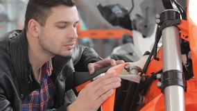 Young man looks at sport motorbike. Close up of man looking at new orange motorbike. Brunete guy touching the gas tank of sport motorbike. Consultant dressed in stock video footage