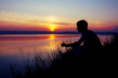 A young man looks at the sunset. A young man sits on the shore of a pond and looks at the sunset Royalty Free Stock Photo